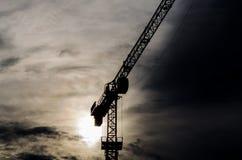 Силуэт крана конструкции с холодной предпосылкой захода солнца Стоковое фото RF