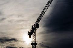 Силуэт крана конструкции с холодной предпосылкой захода солнца Стоковые Фото