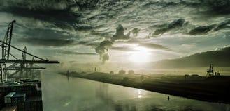 Силуэт кранов и корабль показывают против пестротканого захода солнца Стоковые Фотографии RF