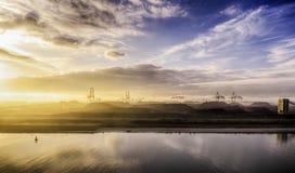 Силуэт кранов показывает против пестротканого захода солнца Стоковые Изображения