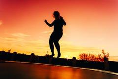 Силуэт красивого плюс девушка молодой женщины размера скача на батут Tr Стоковая Фотография RF