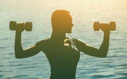 Силуэт красивого спортсмена, который включили в спорт, проведения тренируя с гантелями в руке, на фоне захода солнца Стоковое Изображение RF