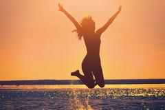 Силуэт красивой, тонкой девушки которая скачет на предпосылку захода солнца Стоковая Фотография RF