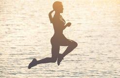 Силуэт красивой тонкой девушки которая скачет на предпосылку захода солнца на пляже Стоковая Фотография