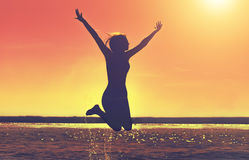 Силуэт красивой, тонкой девушки которая скачет на предпосылку захода солнца на пляже Стоковое Фото