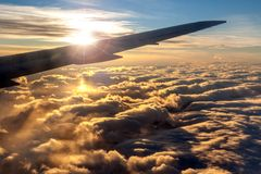 Силуэт крыла самолета против золотого восхода солнца Стоковое Изображение RF