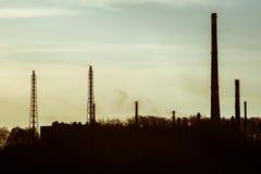 Силуэт куря завода пускает по трубам против неба Стоковые Фотографии RF