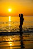 Силуэт к красивой девушке на заходе солнца Стоковые Изображения RF