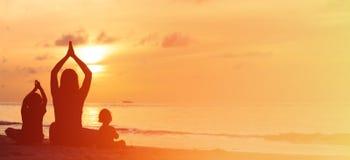 Силуэт матери и детей делая йогу на заходе солнца Стоковая Фотография