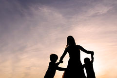 Силуэт матери и детей танцуя на заходе солнца Стоковые Изображения RF