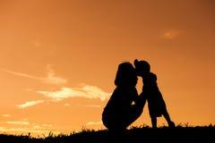 Силуэт матери и сына играя outdoors на заходе солнца с космосом экземпляра стоковые изображения rf