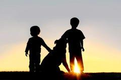 Силуэт маленьких ребеят с собакой Стоковые Фото