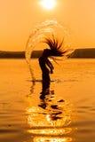 Силуэт маленькой девочки в воде брызгая их волосы Стоковое Изображение RF