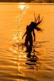 Силуэт маленькой девочки в воде тот брызгать их волосы Стоковое Фото