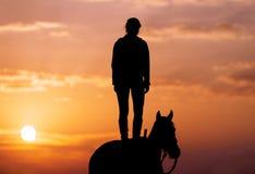 Силуэт маленькой девочки которая стоит на лошади и смотрит в расстояние стоковое фото rf