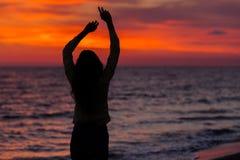 Силуэт маленькой девочки, скача с silk тканью против захода солнца моря Стоковое фото RF