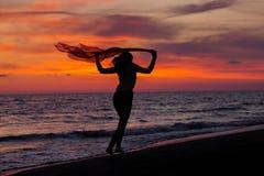 Силуэт маленькой девочки, скача с silk тканью против захода солнца моря Стоковые Изображения RF