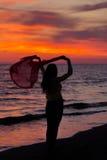 Силуэт маленькой девочки, скача с silk тканью против захода солнца моря Стоковые Фото