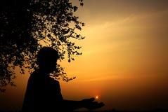 Силуэт мальчика играя на заходе солнца Стоковое Изображение RF