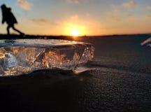 Силуэт мальчика и льда на времени захода солнца морского побережья Стоковое Фото