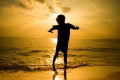 Силуэт мальчика скача над солнечностью волны пляжа Стоковые Фотографии RF