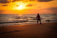 Силуэт молодого мальчика играя футбол на пляже в sunse Стоковые Изображения