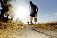 Силуэт молодого человека спорта бежать с конкуренции по пересеченной местностей дороги на заходе солнца лета Стоковое фото RF