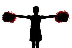Силуэт молодого чирлидера держа ее pompoms прямой o Стоковые Фото