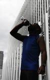 Силуэт молодой бутылки питьевой воды человека спорта после идущей встречи в финансовом районе Стоковые Фото