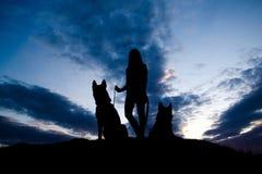 Силуэт молодой женщины и собаки против неба Стоковые Изображения RF