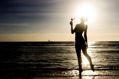 Силуэт молодой женщины на предпосылке захода солнца Стоковая Фотография RF