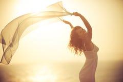 Силуэт молодой женщины ослабляя на пляже Стоковое Фото