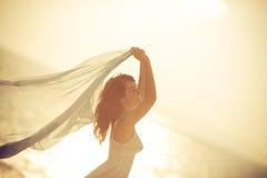 Силуэт молодой женщины ослабляя на пляже Стоковые Фото