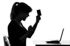 Силуэт молодой женщины получает bonusefrom онлайн приобретение стоковые фото