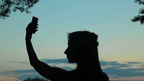 Силуэт молодой женщины принимая selfie с ее телефоном после захода солнца акции видеоматериалы