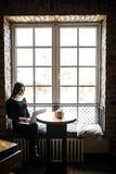 Силуэт молодой женщины сидя на таблице перед окном и компьтер-книжкой польз Работа коммерсантки он-лайн Стоковые Изображения RF