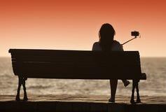 Силуэт молодой женщины сидя самостоятельно на стенде Стоковое Изображение