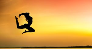 Силуэт молодой женщины скача на заход солнца стоковые фотографии rf