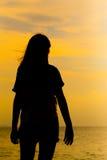 Силуэт молодой женщины стоя на ослабляет представление представления или свободы или представление холодка Стоковые Фотографии RF