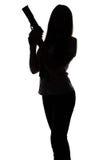 Силуэт молодой женщины шпионки с оружием стоковая фотография rf