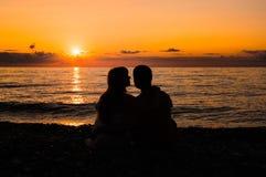 Силуэт молодой романтичной пары смотря заход солнца Стоковая Фотография RF