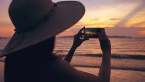 Силуэт молодой туристской женщины в шляпе принимая фото с мобильным телефоном во время захода солнца в пляже океана сток-видео