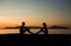 силуэт Молодой человек и женщина сидят совместно на заходе солнца Стоковое Изображение RF