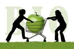Женщины воюя для caddy покупкы с био яблоком Стоковое Фото