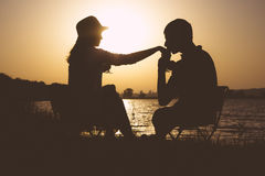 Силуэт назначения молодых пар в влюбленности, который нужно выйти на пикник из городка на зоре стоковые изображения rf
