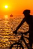 Силуэт нерезкости движения мужского велосипедиста морским путем в заходе солнца Стоковые Изображения RF