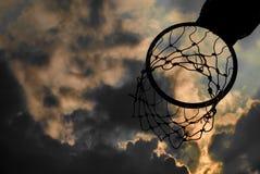 Силуэт обруча баскетбола с драматическим небом Стоковые Изображения RF