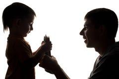 Силуэт отношений семьи, отец дает карандаш цвета ребенка Стоковые Фотографии RF
