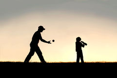 Силуэт отца и маленького ребенка играя бейсбол снаружи Стоковая Фотография