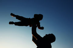 Силуэт отца и сын играют на заходе солнца Стоковая Фотография RF